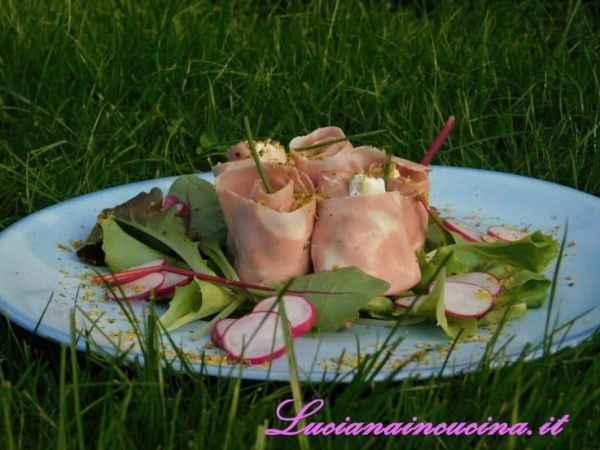 Preparare un letto di insalatina dove adagieremo i rotolini di Mortadella decorando con pistacchi tritati e fettine di rapanello.