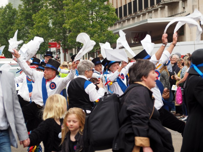 Some men dancing on the Faggots' parade. They seem to not belong there.