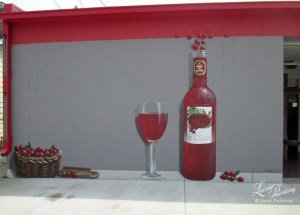 The basket, cranberries, wine glass and bottle are painted to appear as if they are in front of the grey wall. Shadows add to the illusion.