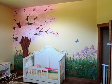 12' tall ceilings afford a very large blooming cherry tree with branches that cascade over a toddler bed. Flowers fill the bottom of the wall.