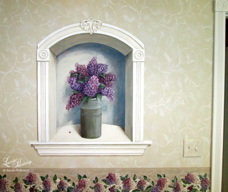 Trompe l'oeil wall niche is painted like a still life painting with lilacs in a vase. Fleur de lis detail on the trim of this alcove bring that special and classical touch in this Victorian home. The light switch plate is painted to blend in with the background wall, which is all painted to look like wallpaper with white swirls on a beige background on the top, and a chair rail border of hydrangeas.