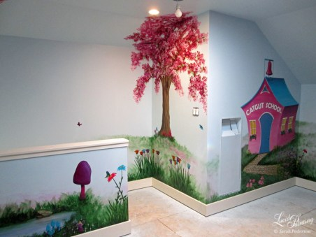 This portion of the fairy playroom features a pond, purple and pink mushroom, and butterflies floating on the walls. A blooming cherry tree is painted at the top of the stairs with tulips near the baseboard trim. A fantasy school, Catgut, is painted on an adjacent wall, and is named after the nearby Catgut Slough in La Crosse, Wisconsin.