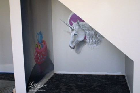 This small space under a staircase will help the children feel like they are in their own little home. A white unicorn with long eyelashes peeks in through a window. The sky in the window is mostly purple, and the teacups are jewel tones of green, yellow, teal, and pink. The little table is a fantasy mushroom with a flat top.