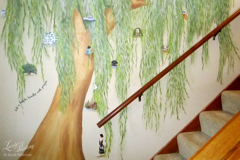 Stylized willow tree painted in a stairwell with numerous miniature elements painted to show my client's memories.