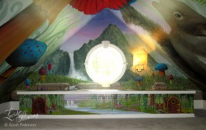 A distant waterfall flows down to a crumbling wall, then flows down to a cabinet that appears to have a recessed top with a stream spelled out in the client's name. Fairies are painted on the front of the cabinet and large mushrooms are painted overhead.