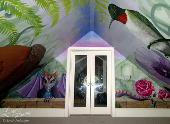 A purple and blue dragon with orange horns peeks into the room above a faux crumbling brick wall. Mountains are seen in the distance and pink roses are growing near her tail. Angled side walls reveal a 3' long ruby-throated hummingbird.