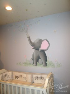 Stylized gray elephant with pink ears sits in grass above a baby crib. Three flowers grow out of the grass. The elephant faces forward with his head pointing to the left. He is blowing swirls out of his trunk, with a variety of flowers, hearts, and stars. Color palette is a variety of pastels. Elements spread out onto the ceiling above the crib.