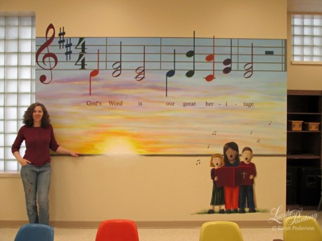 Large mural shows a sunrise at the base and a hymn at the top. The sunrise includes blues, purples, oranges, and yellows..