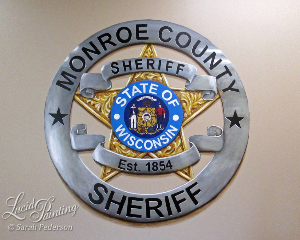 Three foot diameter sheriff's badge appears three dimensional with shadows and reflections. Outside border looks like silver, and inner star looks like gold. Wisconsin state seal is in the center, painted in full detail.