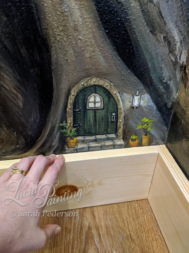 Miniature mouse door appears in the roots of a family tree mural.