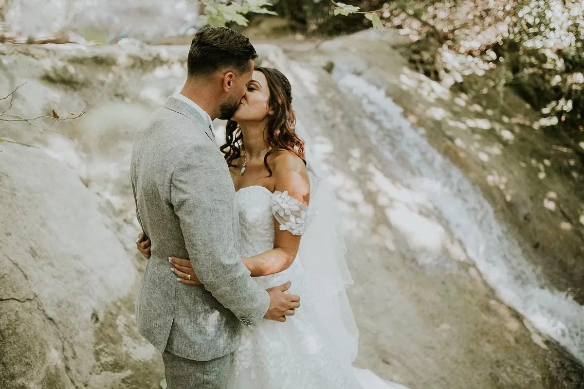 cheveux long détachés bouclés de la mariée en photo de couple devant une cascade d'eau