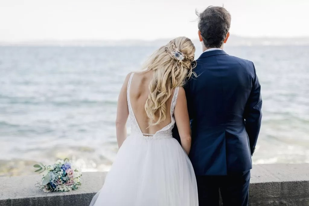 coiffure cheveux détaché long blonde bouclés romatique mariée qui regarde la mer