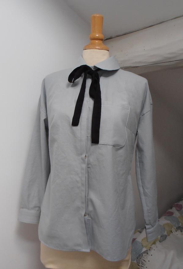 Chemise Mélilot à manches longues en chambray gris bleu sur mannequin de couture. Un nœud noir est noué autour du col claudine.
