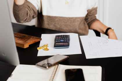 crop woman using calculator while counting bills in workspace