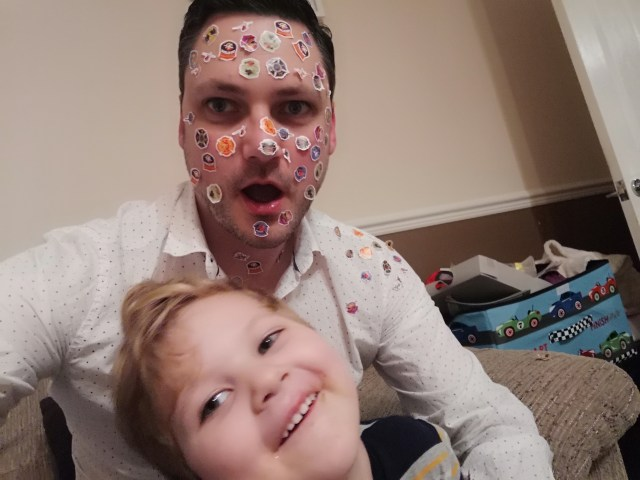 Gregory smiling with my face covered in stickers