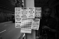 Man putting up notices, Hong Kong