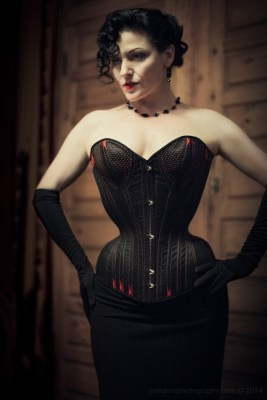 "Dark Garden owner Autumn Adamme models her own corset made under the instruction of Mr. Pearl. Note the distinctive ""Pearlescent"" hip spring and silhouette."