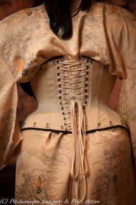 "Prior Attire has made this butterscotch yellow demibust corset with an impressive hip spring; part of her 2015 Geisha corsetry collection. (The flossing says ""woman""!)"