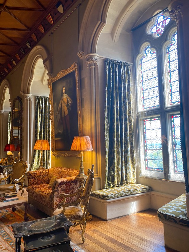 large stained glass windows, bench seats and ornate painitngs and furniture in a room inside the castle