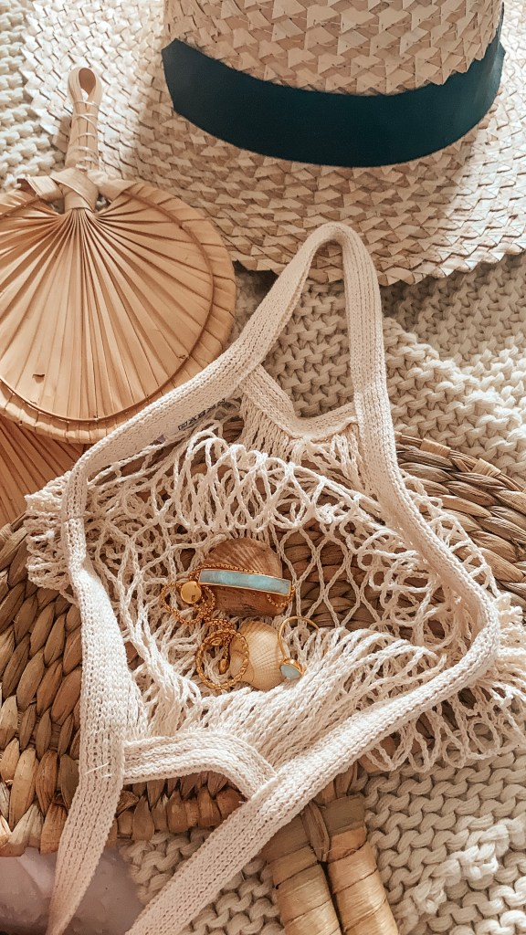 the MV jewellery in a net bag with various neutral things around it
