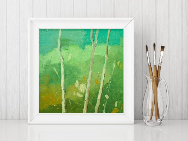 Painting framed next to artist paint brushes in a glass