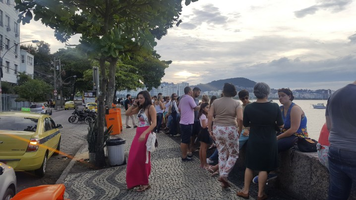 People sitting on the wall in Urca having a drink
