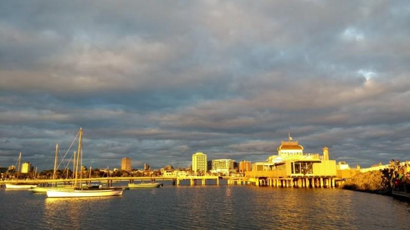 Vivere a Melbourne: cielo plumbeo al tramonto su un molo illuminato di luce gialla