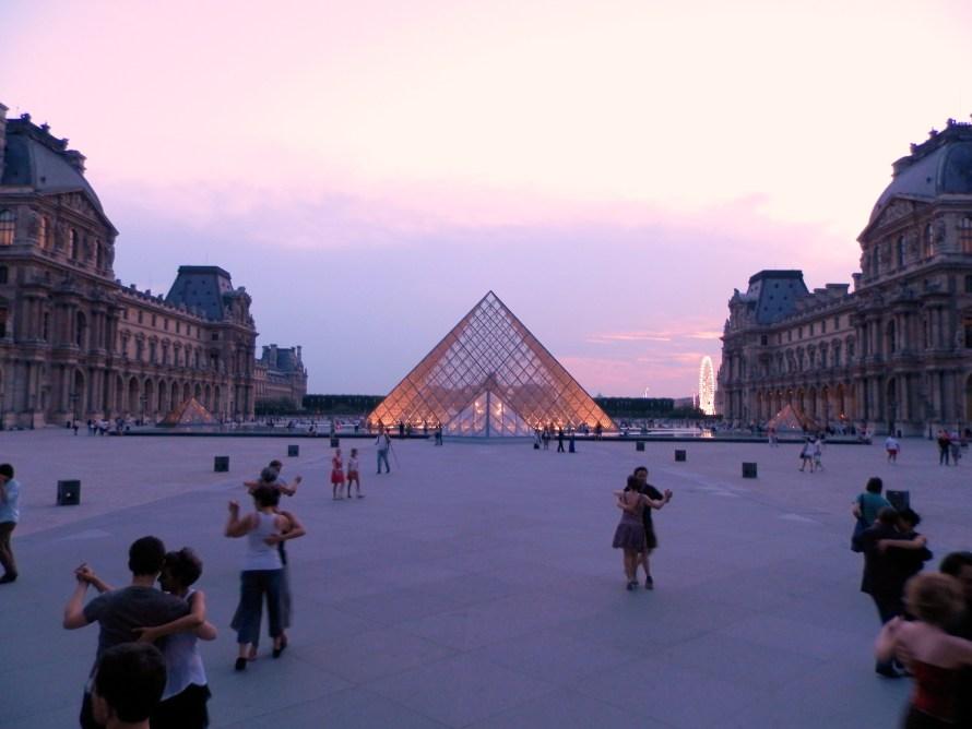 Parigi, coppie che ballano davanti alla piramide del Louvre