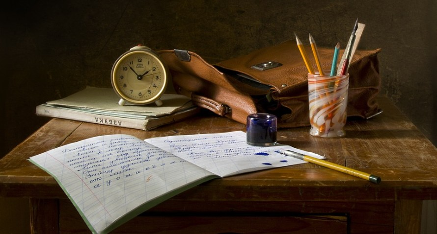 scrivania con quaderni e pennino