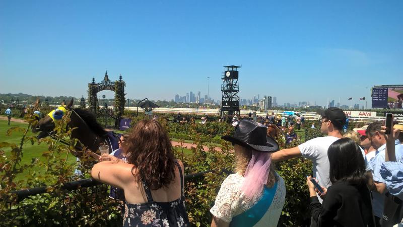 Spettatori che guardano le corse dei cavalli al Flemington Racecourse di Melbourne, con skyline sullo sfondo