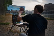 Near Ponte Sant'Angelo. Anton Khubakov, a russian painter, is painting a canvas along the bank of the river.