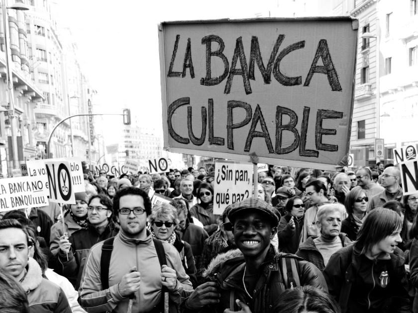 """Manifestantes con pancarta contra la banca: """"Banca Culpable"""". Manifestación en Madrid contra los recortes del Partido Popular y el desmantelamiento del Estado de Bienestar en España. Fotografía de Luis F. Roncero."""