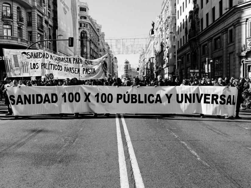 """Marea blanca en la Gran Vía de Madrid con una gran pancarta: """"SANIDAD 100 X 100 PÚBLOCA Y UNIVERSAL"""" Manifestación en Madrid contra los recortes del Partido Popular y el desmantelamiento del Estado de Bienestar en España. Fotografía de Luis F. Roncero."""