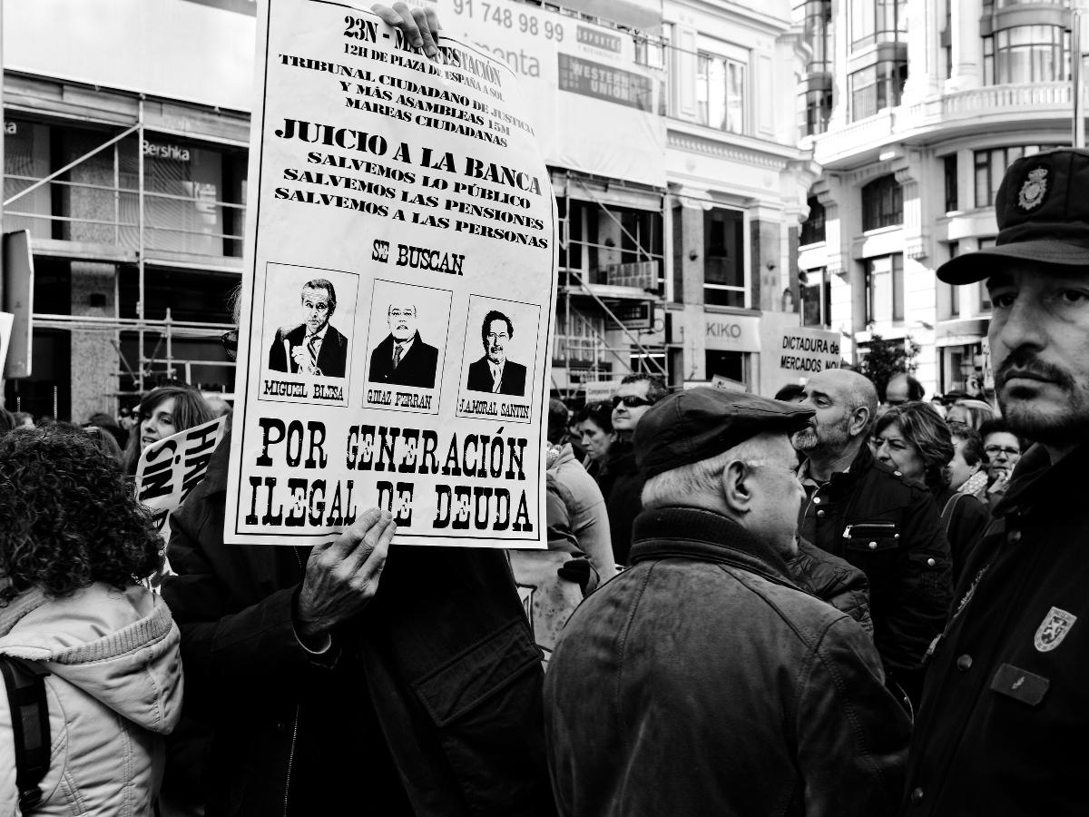 """Policía junto a pancarta: """"JUICIO A LA BANCA. SALVEMOS LO PÚBLICO. SALVEMOS LAS MPENSIONES. SALVEMOS A LAS PERSONAS. SE BUSCAN: MIGUEL BLESA, DÍAZ FERRÁN, MORAL SANTÍN. POR GENERACIÓN ILEGAL DE DEUDA"""". Manifestación en Madrid contra los recortes del Partido Popular y el desmantelamiento del Estado de Bienestar en España. Fotografía de Luis F. Roncero."""