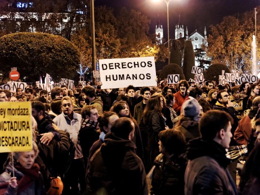 """Joven entre multitud de manifestantes sostiene una pancarta: """"DERECHOS HUMANOS"""" Rodea el Congreso: manifestación en Madrid contra la Ley Mordaza del Partido Popular. Fotografía de Luis F. Roncero."""