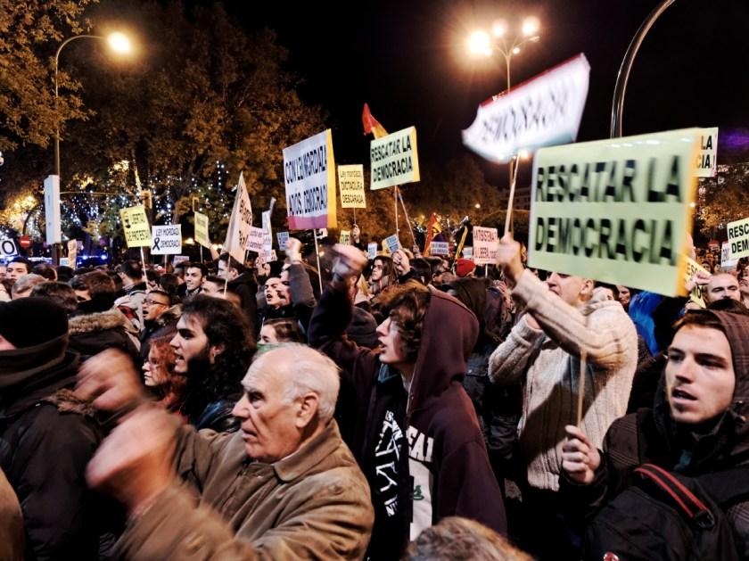 """Manifestantes gritando. En una pancarta se lee: """"RESCATAR LA DEMOCRACIA"""". Rodea el Congreso: manifestación en Madrid contra la Ley Mordaza del Partido Popular. Fotografía de Luis F. Roncero."""