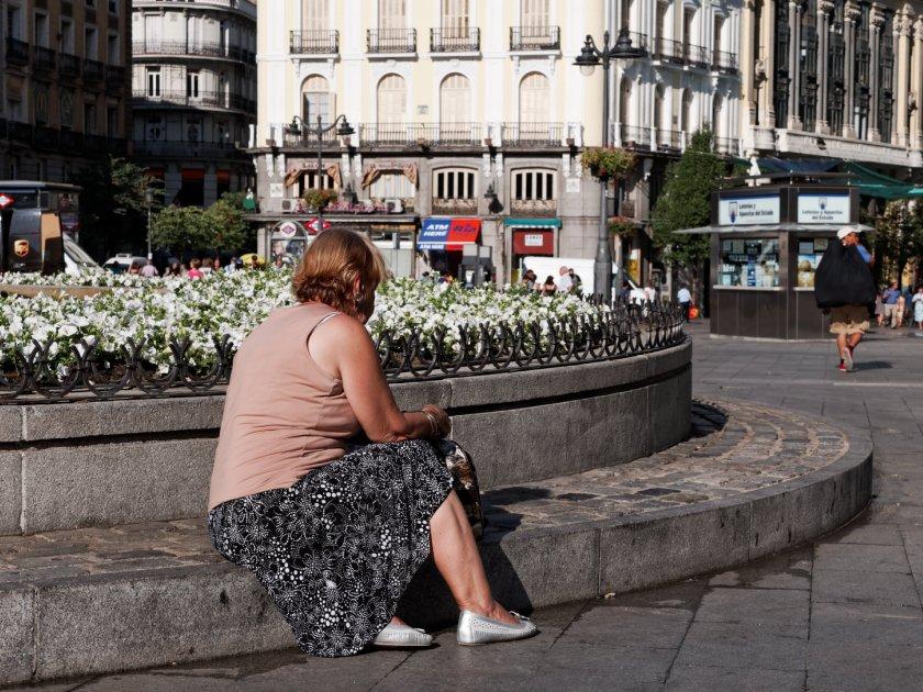 Mujer sentada en un bordillo ante la ausencia de bancos. Puerta del Sol de Madrid. Fotografía de Luis F. Roncero.