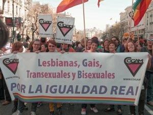 """Activistas de COGAM sostienen pancarta: """"Lesbianas, Gais, Transexuales y Bisexuales por la igualdad real"""". Manifestación el Día Internacional de la Mujer en Madrid. By Luis F. Roncero"""