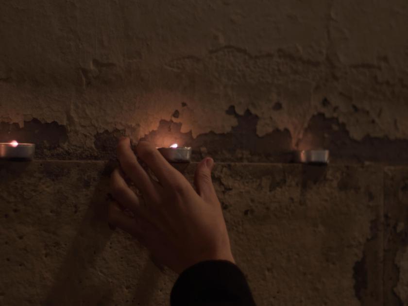 Una mano depositando una vela en la repisa de la pared de una iglesia. Fotógrafo: Luis F. Roncero.