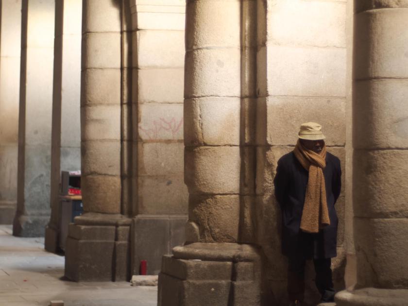 Vagabundo con bufanda y gorro apoyado en una columna de la Plaza Mayor de Madrid. Fotógrafo: Luis F. Roncero.