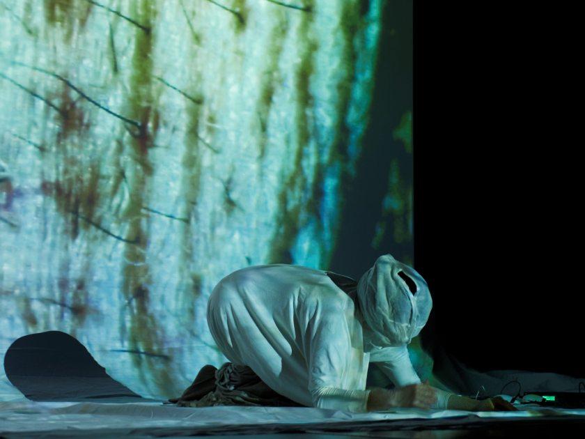 """Mujer rezando con la cara cubierta. Claudia Robles-Ángel representando la performance audiovisual """"SKIN"""" en el festival Madatac. Fotografía de Luis F. Roncero."""