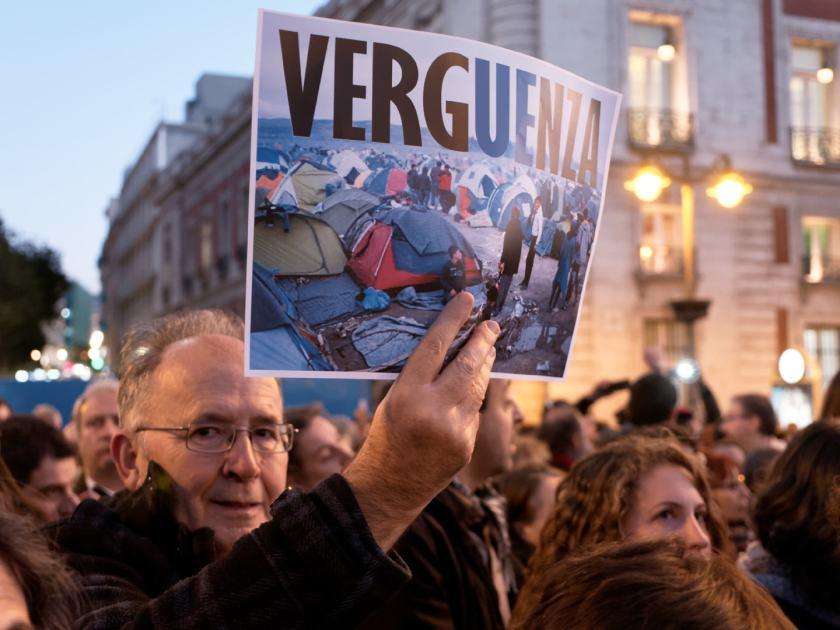 Hombre sostiene pancarta contra la actueción de la Unión Europea durante la crisis de los refugiados sirios. Manifestación por los derechos de los refugiados en la Puerta del Sol de Madrid. Fotografía de Luis F. Roncero.