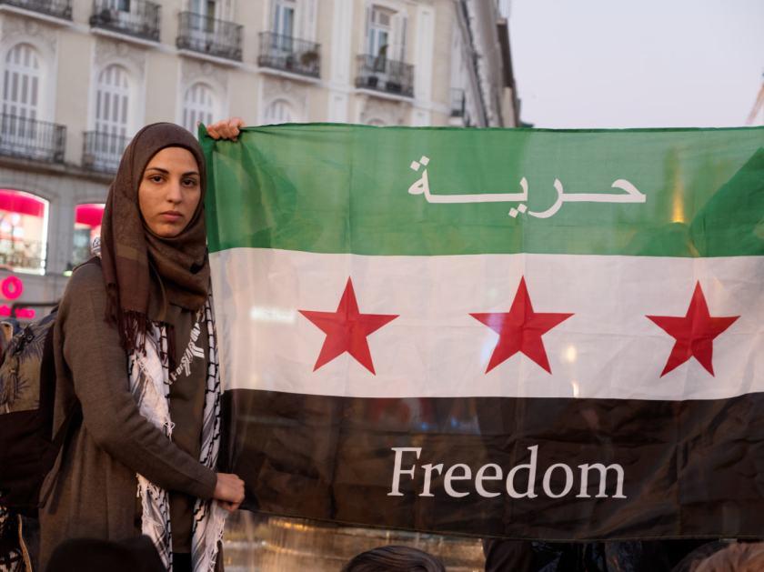 """Mujer con velo sostiene bandera siria con el texto """"Freedom"""" escrito sobre ella. Manifestación por los derechos de los refugiados en la Puerta del Sol de Madrid. Fotografía de Luis F. Roncero."""