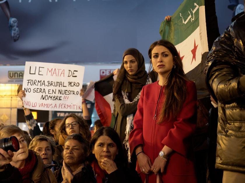 Mujeres se manifiestan delante de una bandera siria. Concentración por los derechos de los refugiados en la Puerta del Sol de Madrid. Fotografía de Luis F. Roncero.