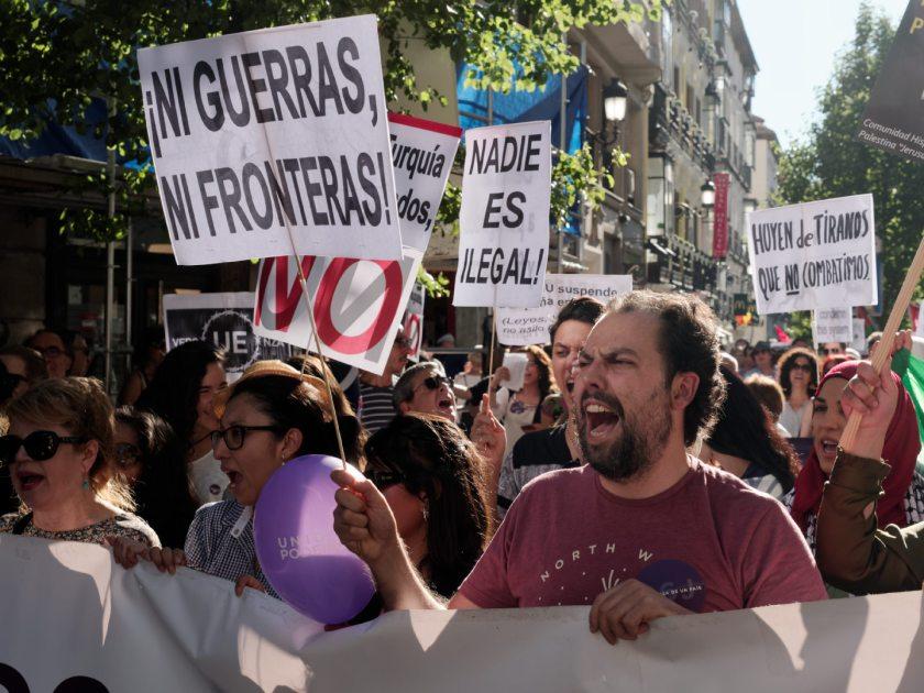 Hombre grita tras una pancarta. Manifestación en Madrid celebrando el Día Mundial del Refugiado. Fotografía de Luis F. Roncero.