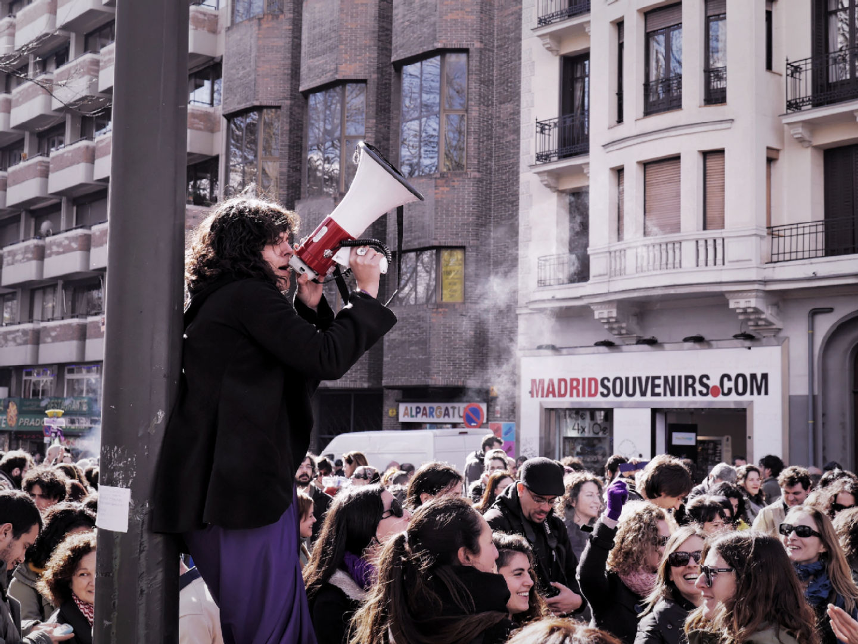 Mujer feminista subida en una valla con un megáfono en la mano. El Tren de la Libertad. Manifestación contra la Ley Gallardón del Partido Popular. Fotografía de Luis F. Roncero.