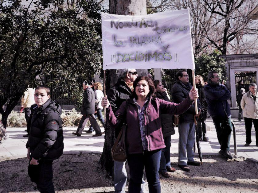 """Mujer sostiene pancarta feminista con el emblema """"Nosotras decidimos"""". El Tren de la Libertad. Manifestación contra la Ley Gallardón del Partido Popular. Fotografía de Luis F. Roncero."""