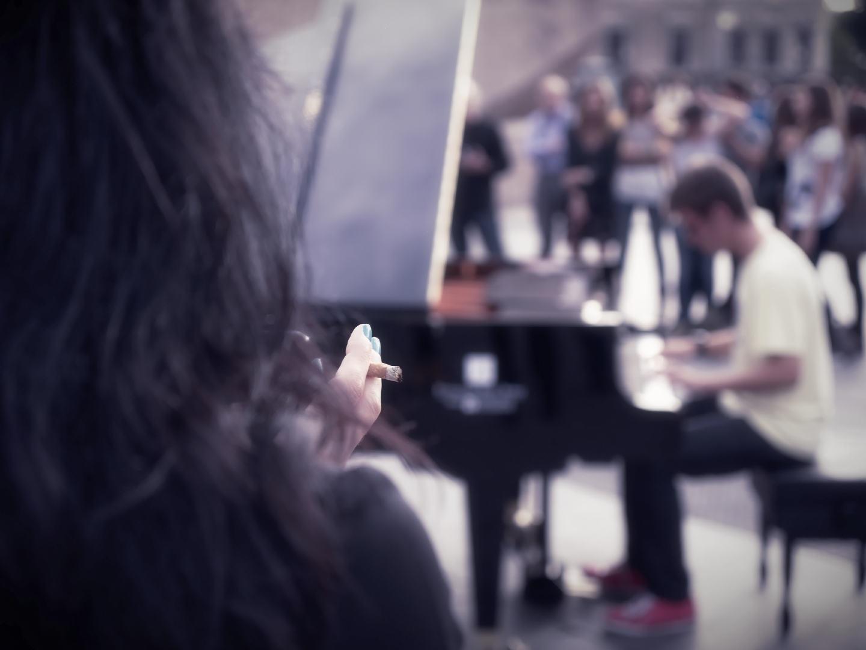 Mujer fumando observa a pianista. Madrid se llena de pianos. Un evento organizado en la Calle Serrano por la Fundación Jesús Serra. Fotografía de Luis F. Roncero.
