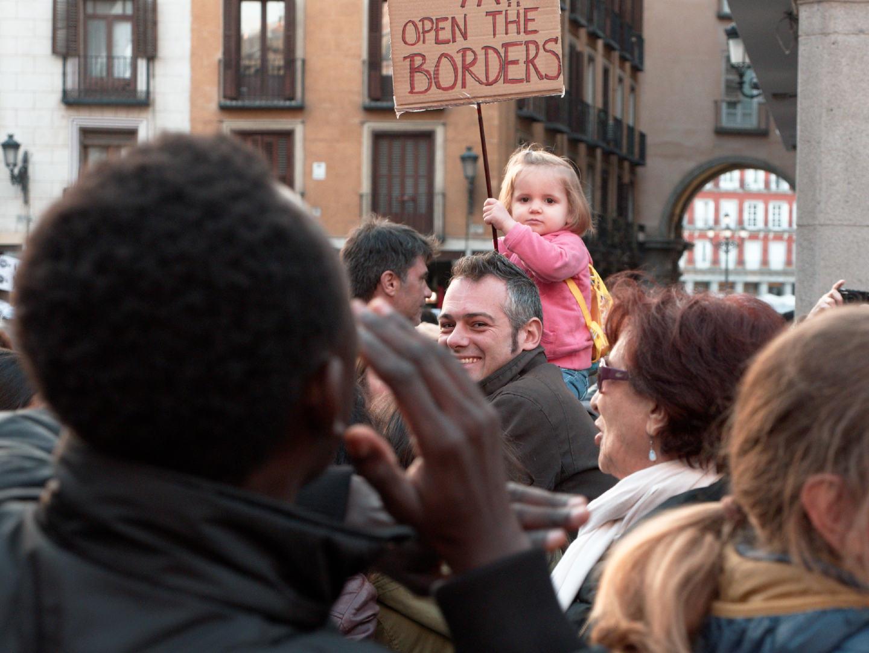Niña rubia sostiene pancarta con el lema OPEN THE BORDERS. Manifestación por los derechos de los migrantes y los refugiados en Madrid. Fotografía de Luis F. Roncero.