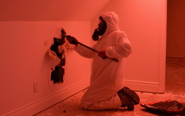An asbestos-abatement worker takes down drywall to access the attic, where there is insulation containing asbestos in Vancouver, March 2016. The soaring number of house demolitions in B.C. has prompted work safety officials to almost double the number of asbestos-prevention officers in the province, a move that could cost an extra $1-million a year.